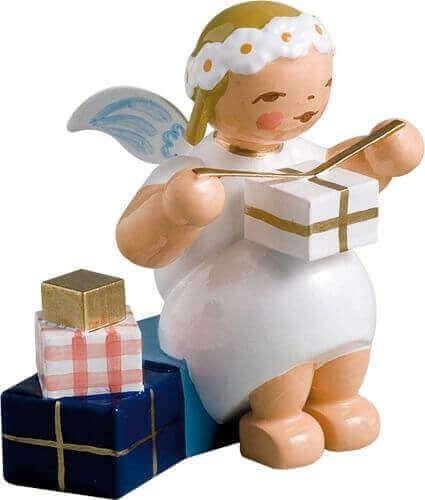 aMargeritenengel, sitzend, mit Geschenken